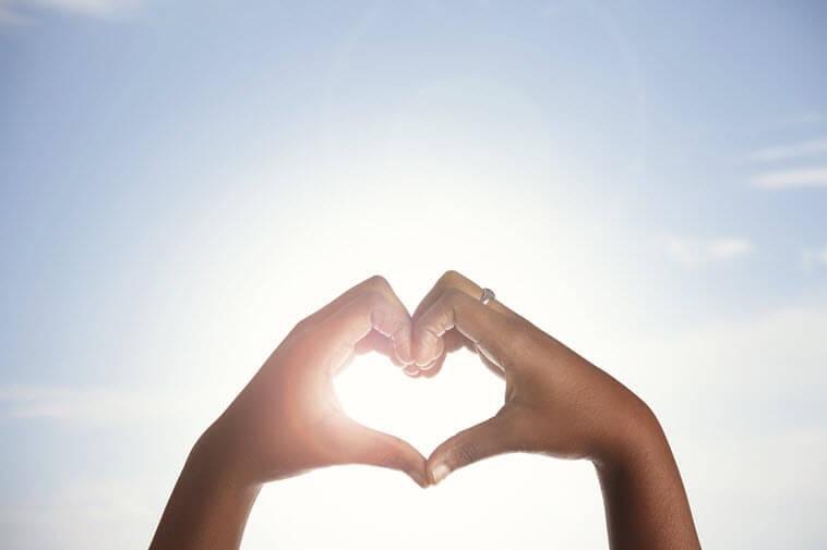 Two hands make a heart shape around a sun -- Advertising Through Stories Blog