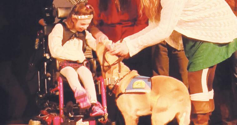 Dog greets girls in wheelchair
