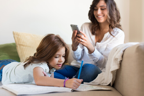 Mom browsing internet on her phone while daughter colors