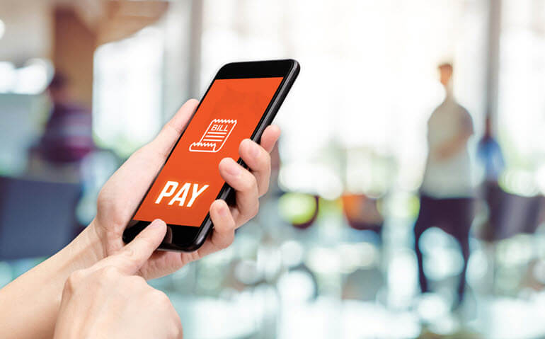 "Hand holding smartphone with ""pay"" on screen"