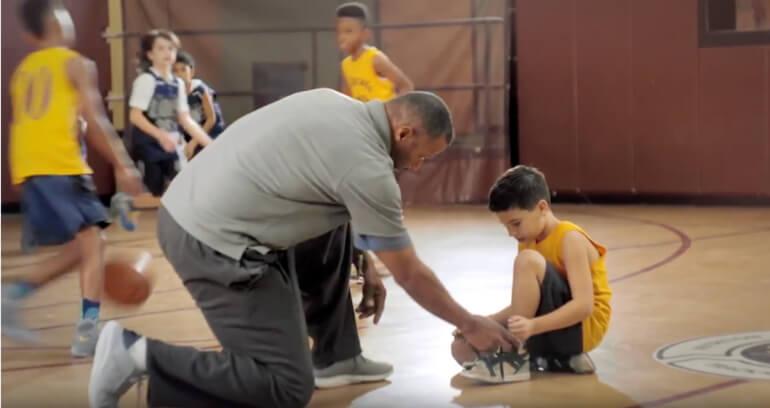 Coach kneeling to help child tie shoelace