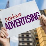 Hands holding up Native Advertising sign