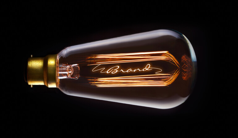 """Light bulb with a filament spelling """"brand"""""""