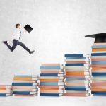 Man bounding up stacks of books toward graduation cap