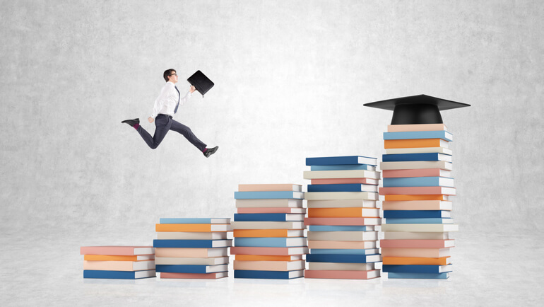 Man bounding up stacks of books toward graduation cap