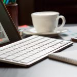 Tablet, keyboard, pen, paper and coffee cup on a desk
