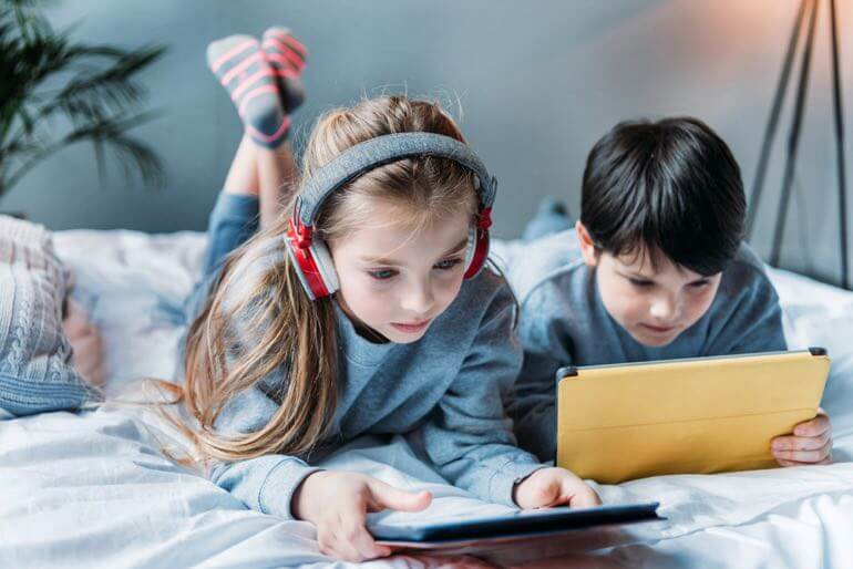 Two kids watching tablets