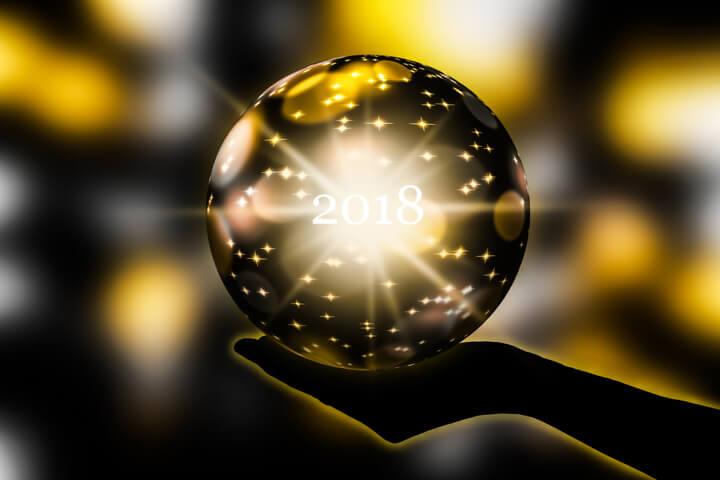 """Hand holding crystal ball displaying """"2018"""""""