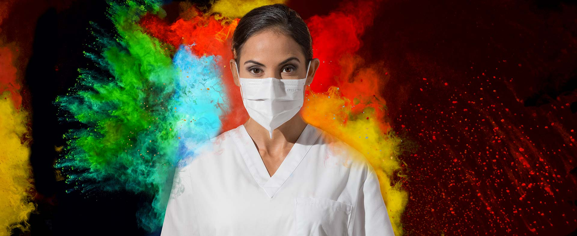 Woman in lab coat wearing Crosstex Mask with colored powder exploding around her