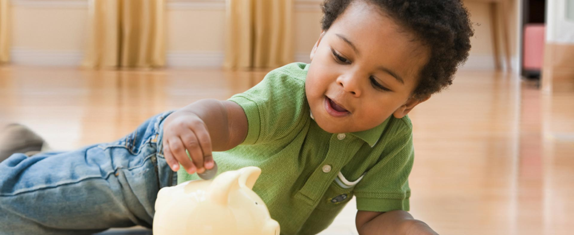 Toddler playing with coins and a piggy bank